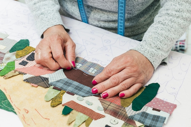 Woman's hand stitching fabric house with needle at workplace Free Photo