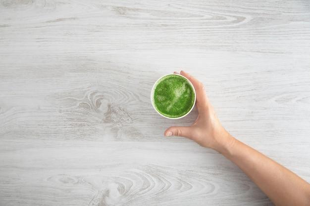 女性の手が、日本のオーガニックプレミアム抹茶ラテを用意した紙ガラスを奪います。白い木製のテーブルの上。上面図 無料写真
