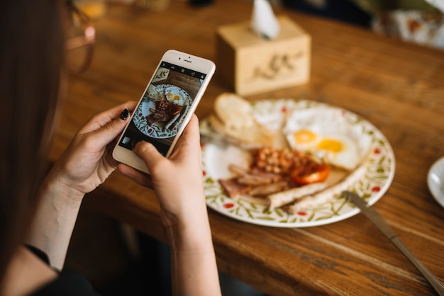 Woman's hand taking photo of breakfast on wooden table through cell phone Free Photo
