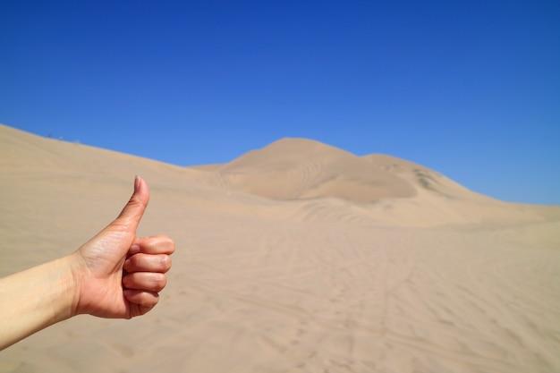 Woman's hand thumbing up to the amazing view of huacachina desert in ica region of peru Premium Photo
