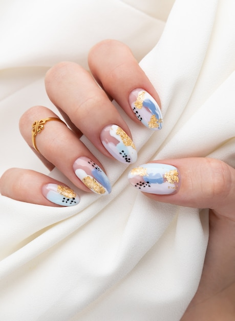 Woman's hand with fashionable nails holding fabric Premium Photo