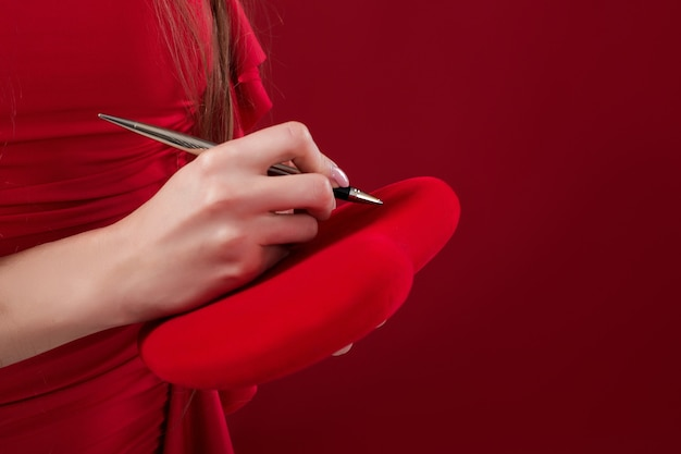 Woman's hand writes with a pen on her heart for st. valentine's day Premium Photo