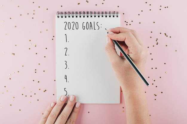Woman's hand writing 2020 goals notebook decorated with christmas decoration Premium Photo