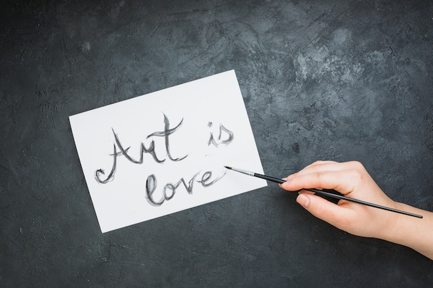 Woman's hand written 'art is love' text on white paper with paintbrush over slate backdrop Free Photo