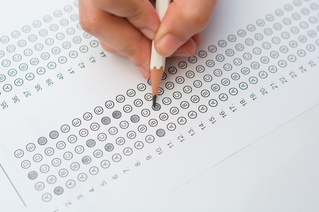 Woman's hands filling in standardized test form Premium Photo