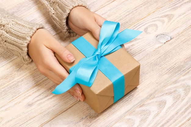 Woman's hands give wrapped valentine holiday handmade present in craft paper with blue ribbon. Premium Photo