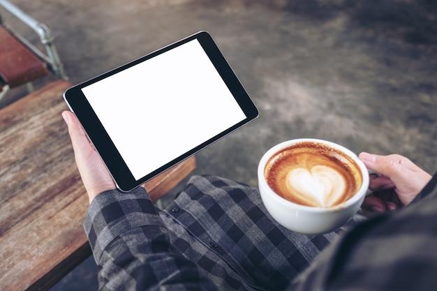 Женские руки держат черный планшетный пк с пустым экраном во время питья кофе в кафе Premium Фотографии