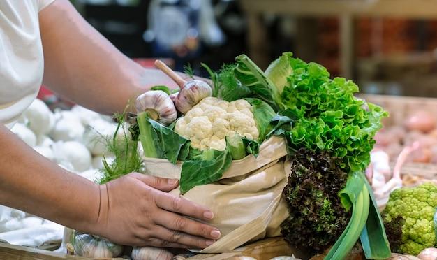 Mani della donna che tengono broccoli organici maturi freschi, insalata con verdure e verdure in sacchetto di cotone al mercato del contadino del fine settimana Foto Gratuite