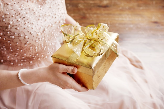 Woman's  hands holding gold gift box. Premium Photo