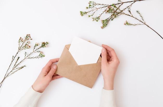 Woman's hands holding kraft envelope with blank wedding invitation card. Premium Photo