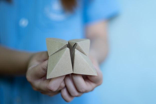 Woman's hands holding a paper fortune teller on blue background Premium Photo
