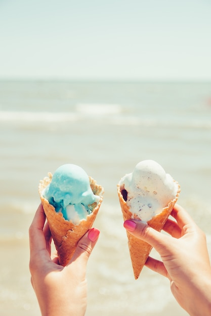 女性の手は海に2つのアイスクリームを保持しています。 Premium写真