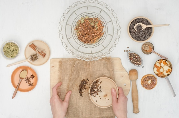 Женские руки готовят индийский чай масала со специями Premium Фотографии