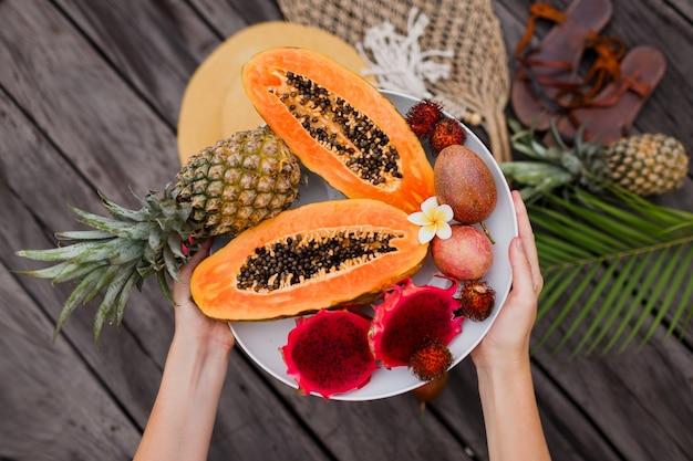 新鮮なエキゾチックなフルーツの大きなプレートを持つ女性の手。 無料写真