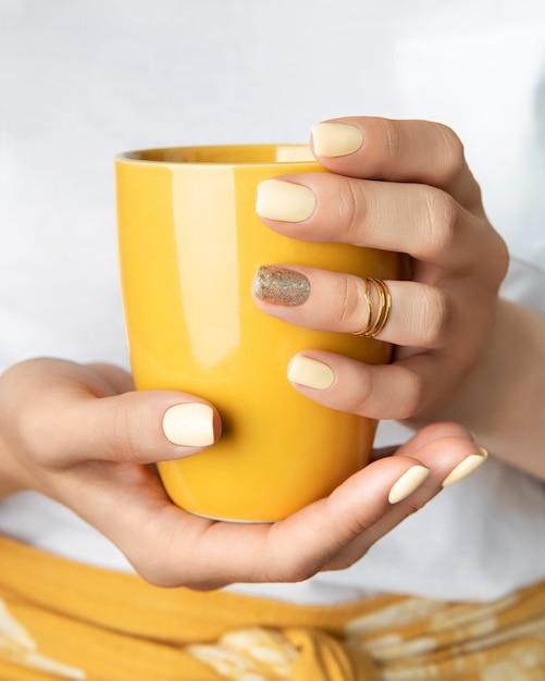 カップを保持している黄色の光沢のあるネイルデザインの女性の手。 Premium写真