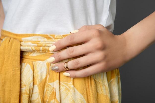黄色の光沢のあるネイルデザインの女性の手。 Premium写真