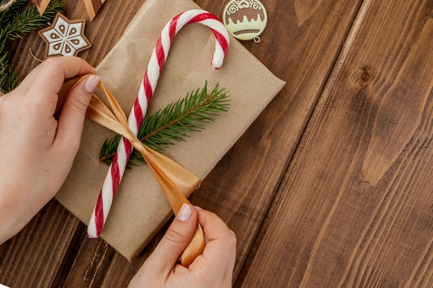 Woman s hands wrapping christmas gift, close up. unprepared christmas presents on wooden  with decor elements and items, top view. christmas or new year diy packing . Premium Photo
