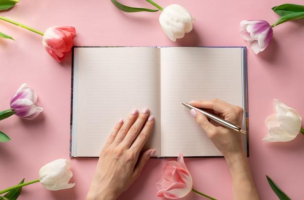 여자의 손에 화려한 튤립의 프레임 분홍색 배경에 빈 노트북에 펜으로 쓰기. 라이프 스타일 부드러운 배경입니다. 프리미엄 사진