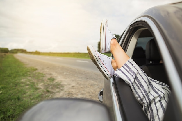 Woman's legs dangling out a car window parked on roadside Free Photo
