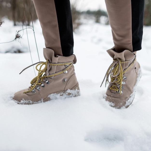 겨울 갈색 가죽 패션 부츠에 세련 된 바지에 여자의 다리는 눈에. 확대. 프리미엄 사진