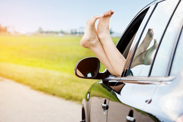 Woman's legs out of the car window Premium Photo