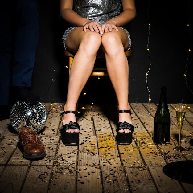 Le gambe della donna in scarpe vicino a palla da discoteca, bottiglia e maschio Foto Gratuite