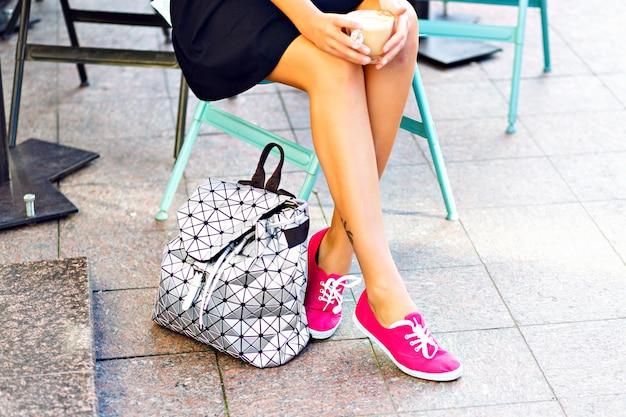 女性のきれいな脚、屋外カフェに座っている女の子、カプチーノ、コーヒーのカップを手に持っています。ピンクの半靴を履き、靴の横にあるスタイリッシュなシルバーのバックパック。 無料写真