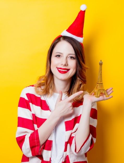Woman in santa claus hat with eiffel tower gift Premium Photo