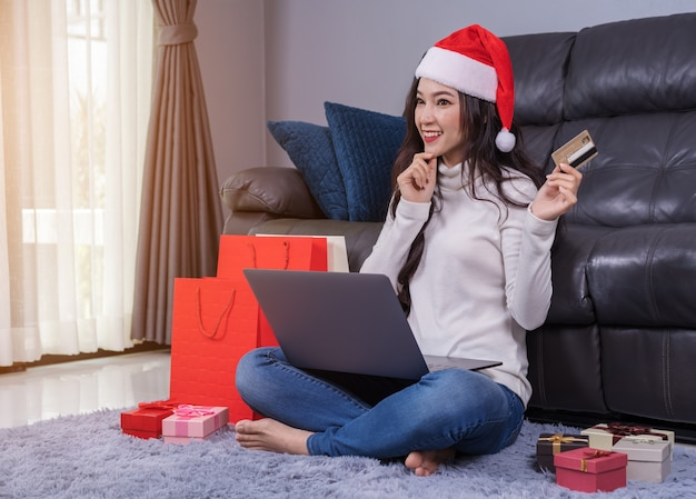 Woman in santa hat thinking about shopping online for christmas gift with laptop in living room Premium Photo