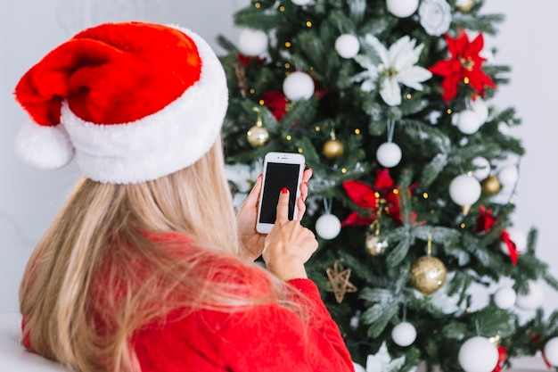 Woman in santa hat with phone Free Photo