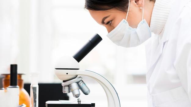 Женщина-ученый с микроскопом Premium Фотографии