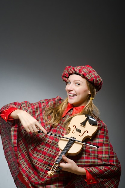 Woman in scottish clothing in musical concept Premium Photo