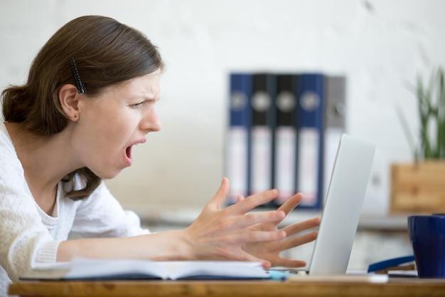 Woman screaming at laptop Free Photo