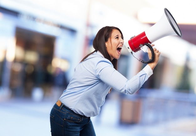 Woman screaming through a megaphone Free Photo