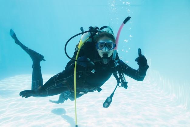 Woman on scuba training submerged in swimming pool showing thumbs up Premium Photo