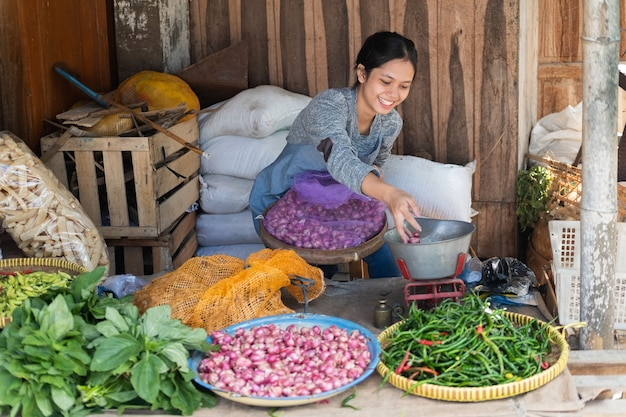 Женщина, продающая овощи, улыбается, сидя с мешком, наполненным луком-шалотом, в овощном ларьке Premium Фотографии