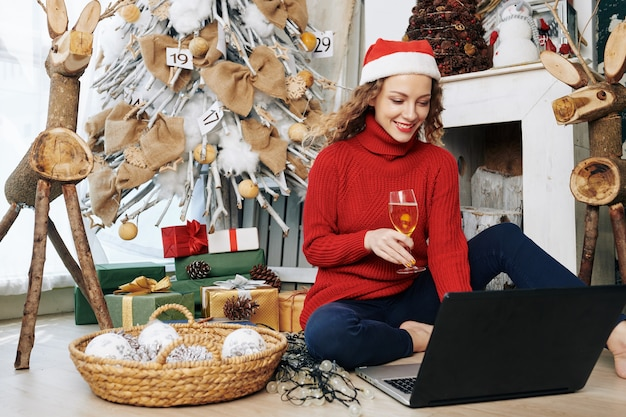 Woman sending e-mails with christmas wishes Premium Photo