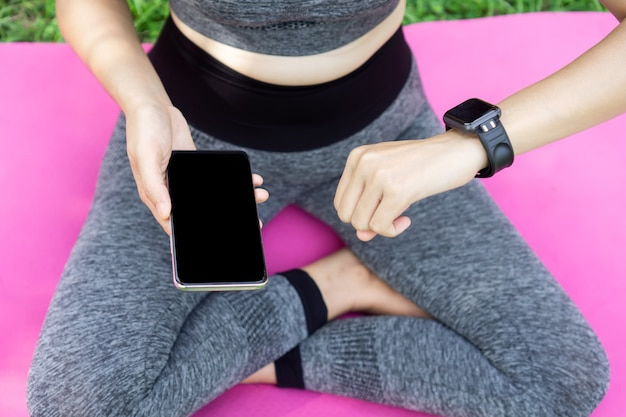 Woman setting smart watch and phone while doing yoga Premium Photo