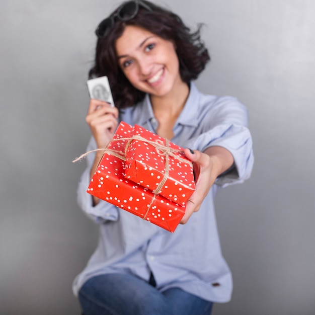 Woman in shirt giving gift box Free Photo