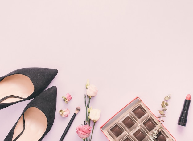 Woman shoes with cosmetics and roses on table Free Photo