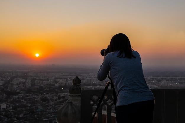 Woman shooting landscape camera on tripod at sunset in hahagarh fort jipur. Premium Photo