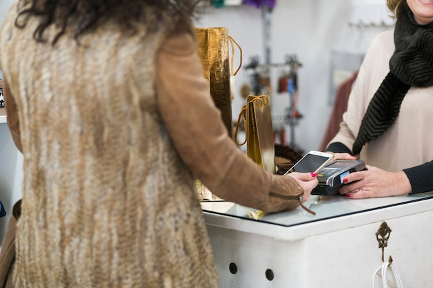 Woman in shop paying with smartphone Free Photo