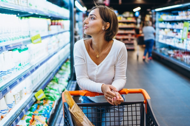 Woman shopping at the grocery store, by the refrigerator Free Photo