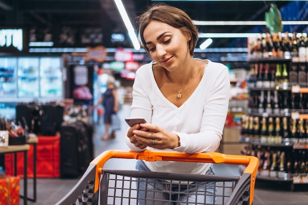 Woman shopping at the grocery store and talking on phone Free Photo