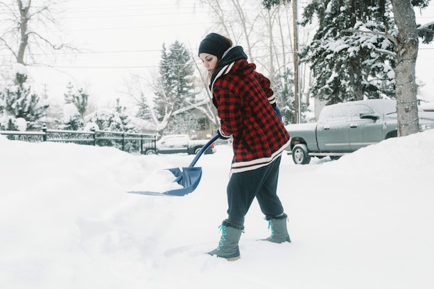 Woman shoveling snow on pine trees background