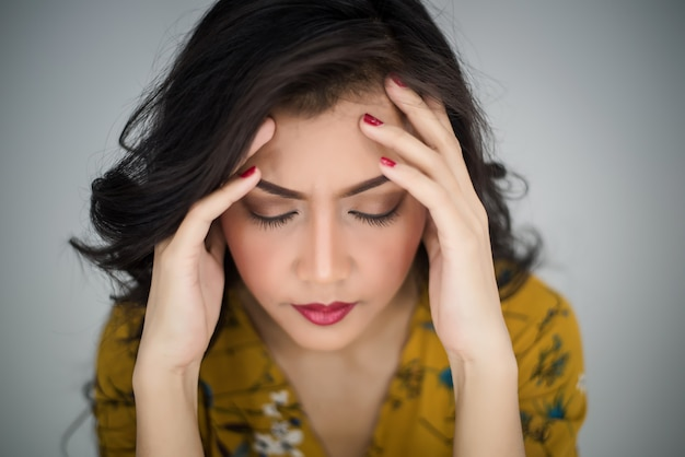 Woman showing acting headache or stress Free Photo