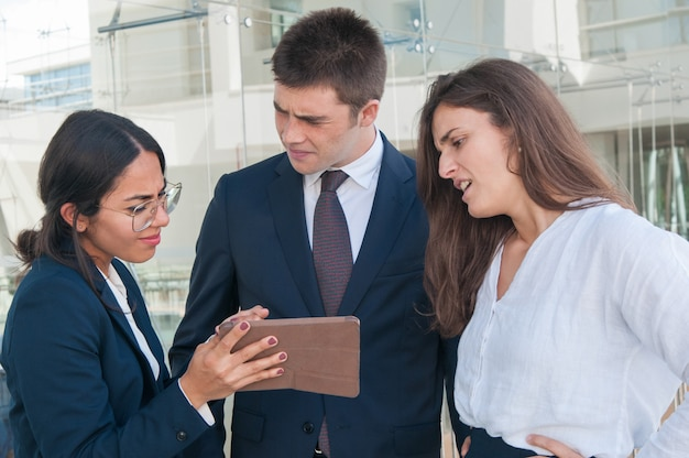 Woman showing data on tablet, colleagues doubting idea Free Photo