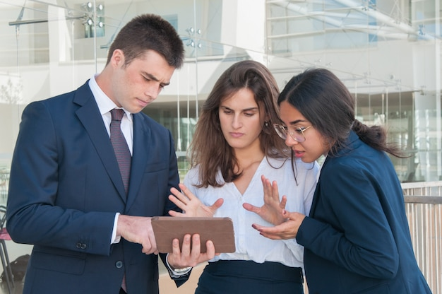 Woman showing data on tablet, everyone looking skeptical Free Photo