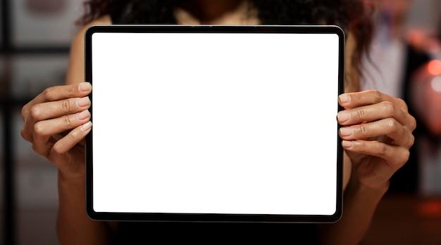 Donna che mostra un tablet schermo vuoto a una festa di capodanno Foto Gratuite