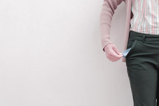 Woman showing her empty pocket on wall background. Premium Photo